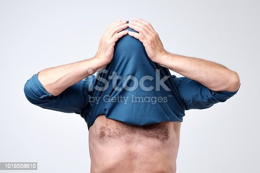 istock Man hiding his face with undershirt. Human hid head with t-shirt 1016558610