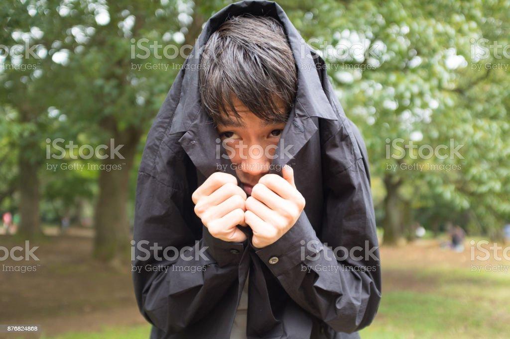 Man hiding in jacket stock photo