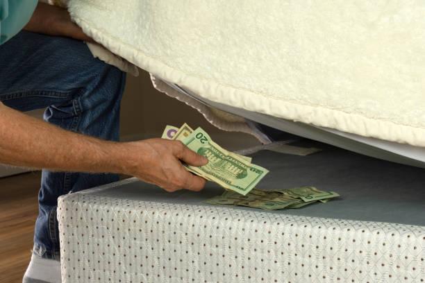 man hiding money under his mattress because he doesn't trust banks - poniżej zdjęcia i obrazy z banku zdjęć