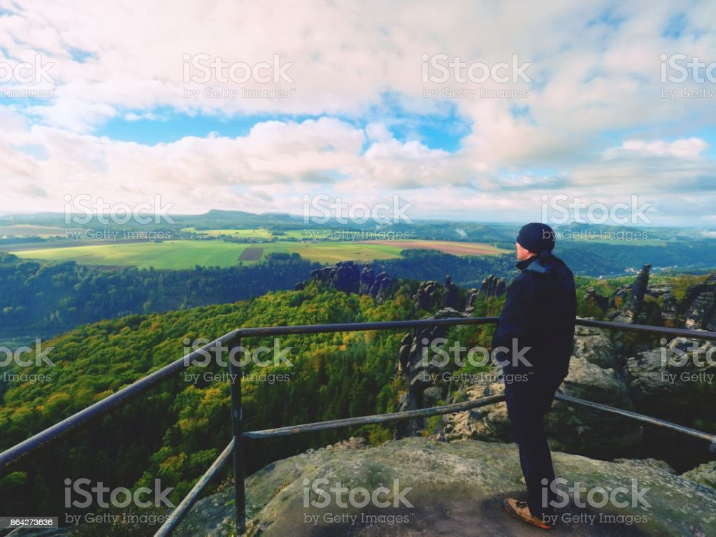 Man hiker at handrail on the peak of rock watching into misty landscape royalty-free stock photo