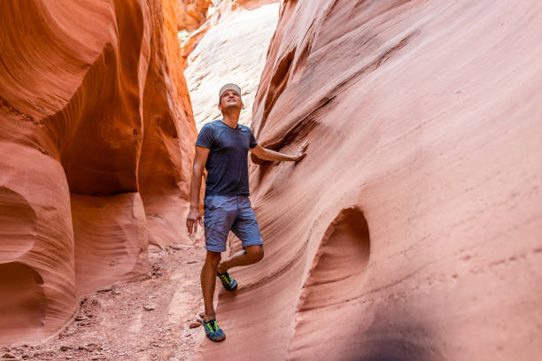 Man hiker looking up touching wall of red wave shape formations at Antelope slot canyon in Arizona on footpath trail from Lake Powell Man hiker looking up touching wall of red wave shape formations at Antelope slot canyon in Arizona on footpath trail from Lake Powell page arizona stock pictures, royalty-free photos & images