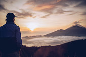 Young man hiker enjoying the view of Mt. Batur and Mt. Agung, Bali, Indonesia