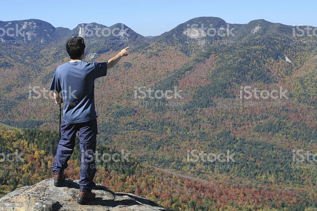 Man Hiker on Mountain Summit and Pointing a Direction royalty-free stock photo