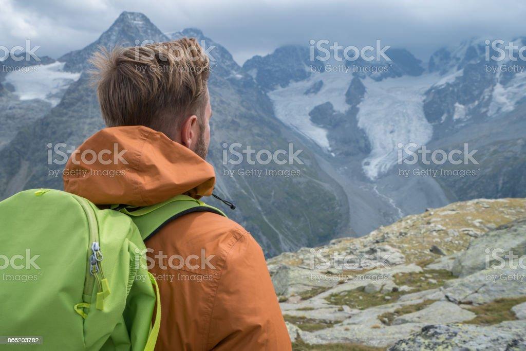 Man hiker on mountain top contemplating spectacular views stock photo