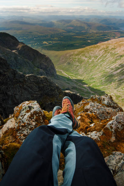 Man hiker sitting on the top of mountain rocks. Beautiful weather with Scotland nature. stock photo