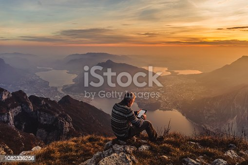 Man hiker solo on the mountain during golden hour reading e-book