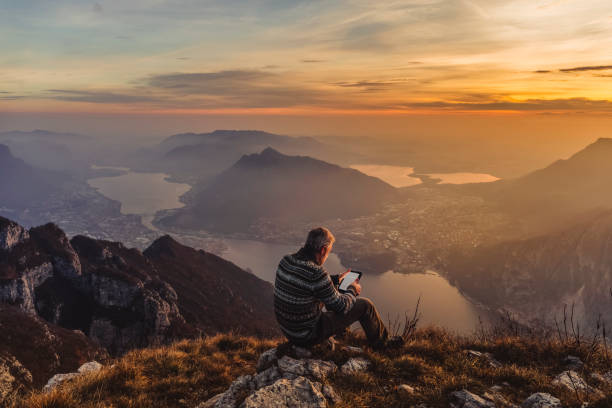 Man hiker solo on the mountain during golden hour Man hiker solo on the mountain during golden hour reading e-book wisdom stock pictures, royalty-free photos & images