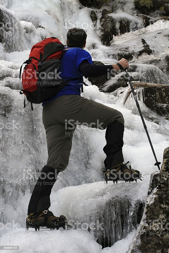Man Hiker Wearing Crampons and Backpack Ice climbing in Trail royalty-free stock photo