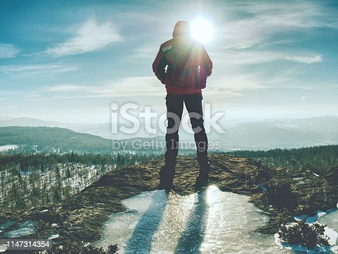 Back view of man hiker with backpack looking to landscape covered snow
