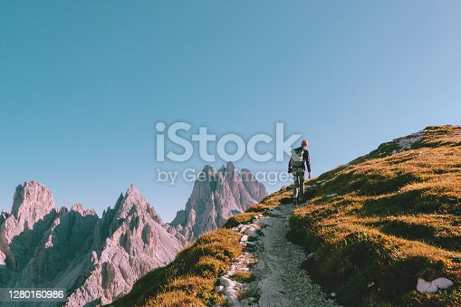 Young man with a backpack, wearing jeans, checkered shirt and yellow hat is hiking on the edge of rock. Rocky mountains and blue cloudless sky is on the background.
