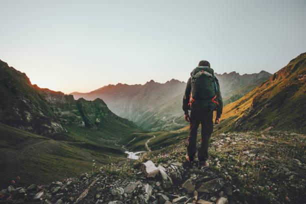 Menschen wandern bei Sonnenuntergang Berge mit schweren Rucksack Reisen Lifestyle Fernweh Abenteuer Konzept Sommerurlaub im freien allein in die Wildnis – Foto