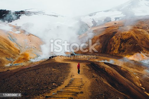 Young man tourist in red jacket enjoying morning hiking at the panoramic geothermal smoking bright colorful mountain land in the wilderness of Iceland Highlands