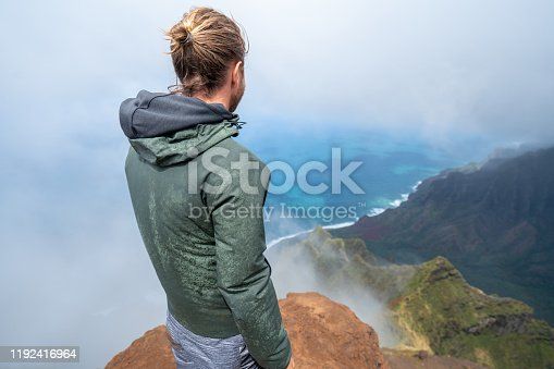 Man hiking in Hawaii contemplates waterfall and lush mountains