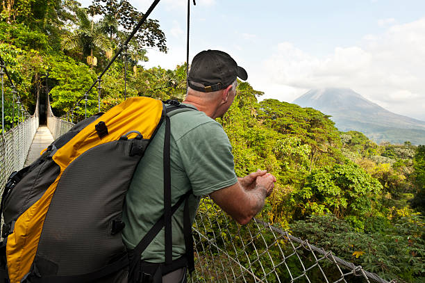男性のジャングルのハイキング、橋、アレナル火山、コスタリカ - 自然旅行 ストックフォトと画像
