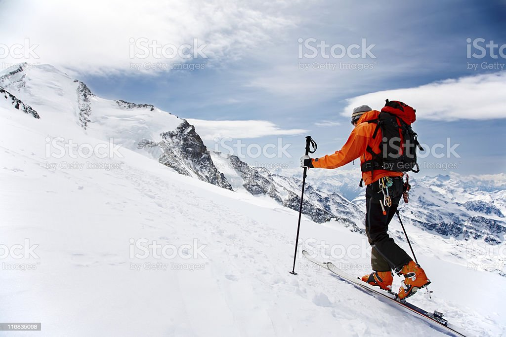 A man hiking in snowshoes up a snowy mountain stock photo