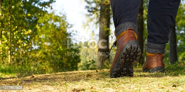 istock Man hiking in the woods in Autumn pine forest. Men boots walking in the woods on sunny day. hiking concept, outdoor lifestyle. 1277857503