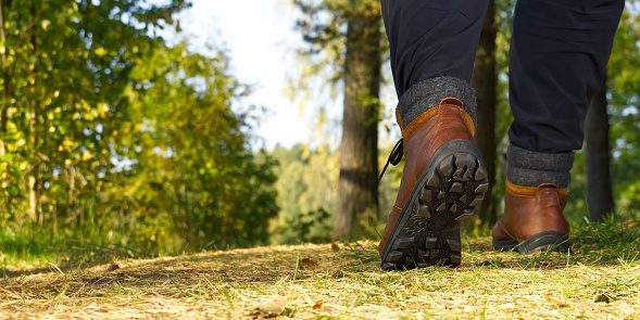 Man hiking in the woods in Autumn pine forest. Men boots walking in the woods on sunny day. hiking concept, outdoor lifestyle. Hiking man with trekking boots on the trai