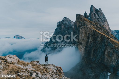 Young Caucasian man  hiking near Seceda mountain in Dolomites