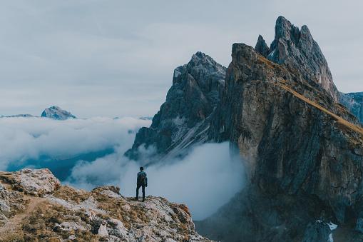 Young Caucasian man  hiking near Seceda mountain in Dolomites