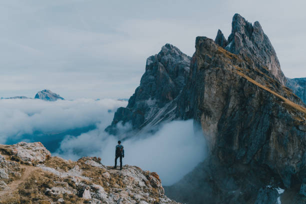 Man hiking near Seceda mountain in Dolomites stock photo