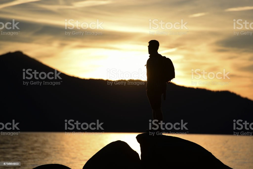 A Man Hiking on Rocks Overlooking a Lake at Sunset royalty-free stock photo
