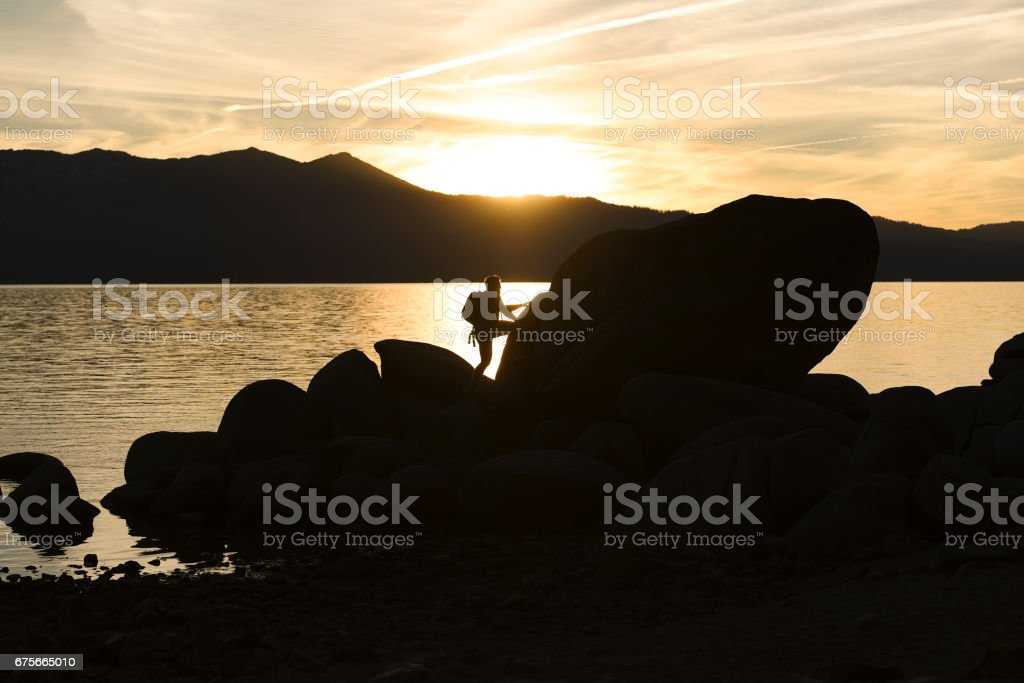 A Man Hiking on Rocks Overlooking a Lake at Sunset stock photo