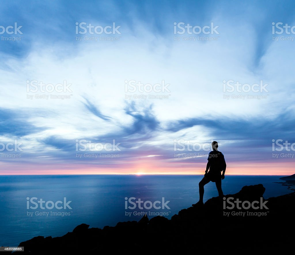Man hiking silhouette in mountains, ocean and sunset stock photo