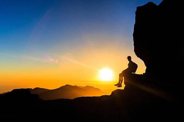 Man hiking silhouette in mountains sunset freedom stock photo