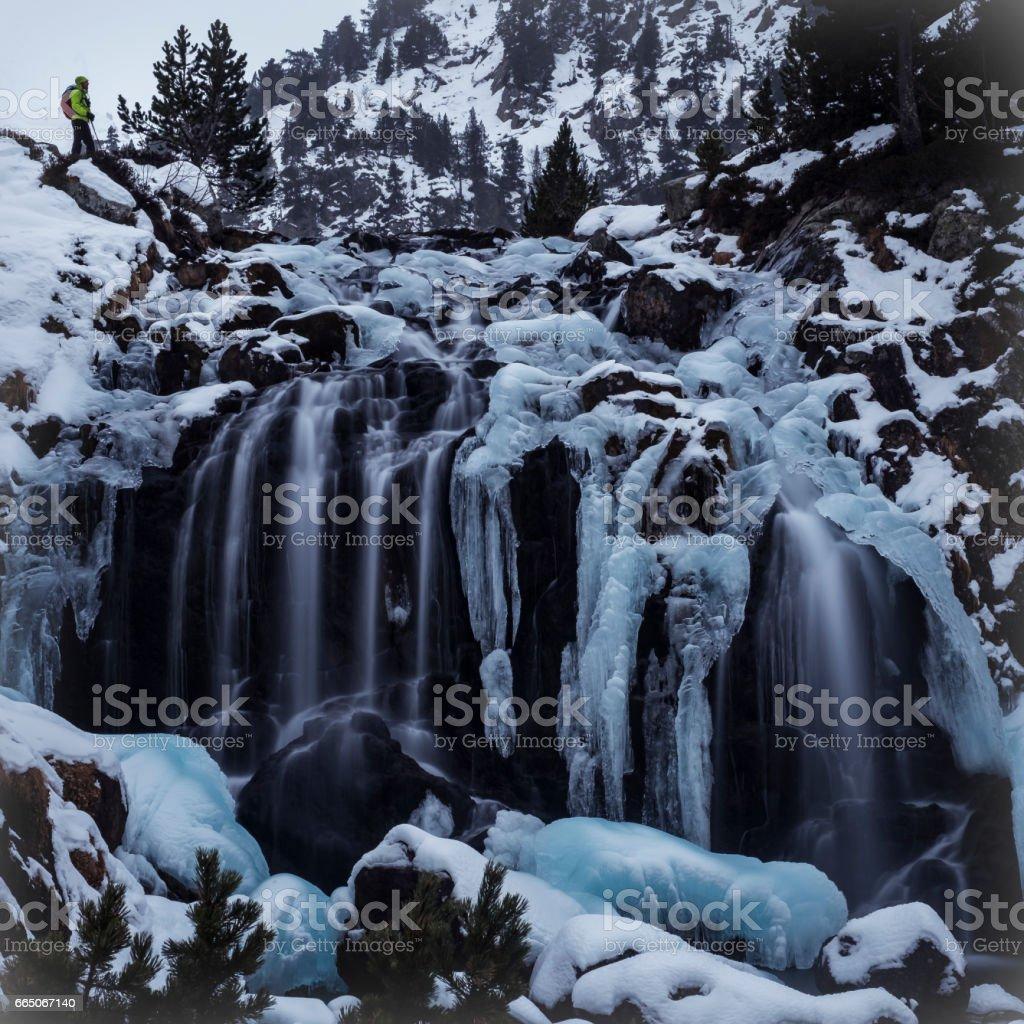 Man hiking to Aigualluts waterfall in winter. Pirineos. Huesca. España. stock photo