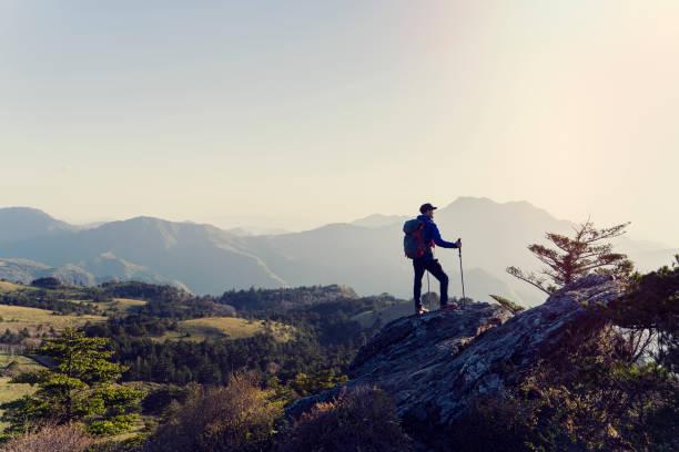 a man hiking with a view from the rock - занятия на открытом воздухе стоковые фото и изображения