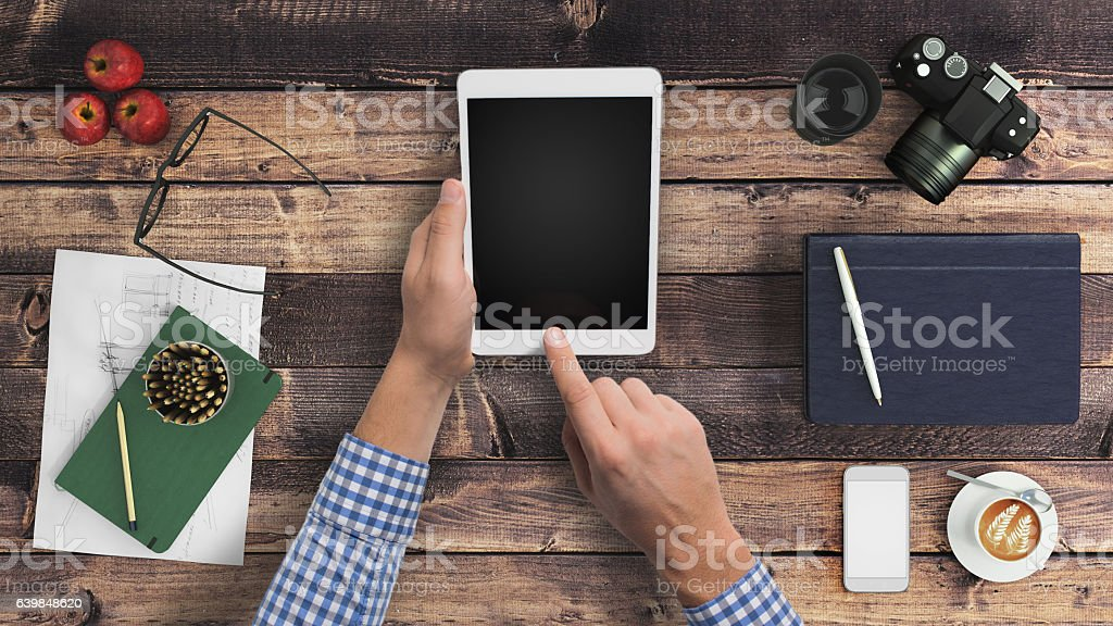 Man hipster holding tablet knolling overhead view stock photo