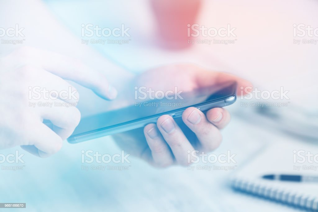 Man Hipster using smartphone a touch screen smart phone hands close up, vintage colors Light toning - Foto stock royalty-free di Composizione orizzontale