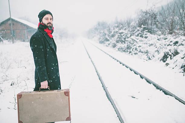 man hipster with old vintage suitcase on railways - festzugskleidung stock-fotos und bilder