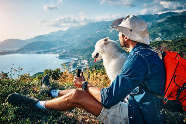 man his best friend taking a break from hiking stock photo