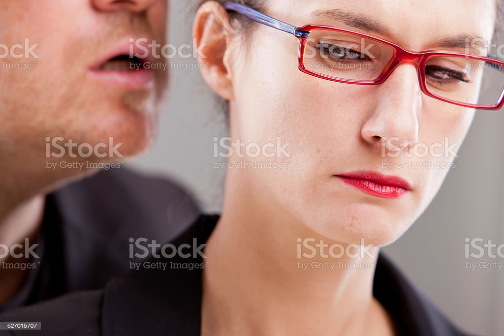 man hissing menaces in woman's ear stock photo