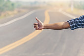 istock Man hitchhiker standing on a road. Adventure and tourism 636316538