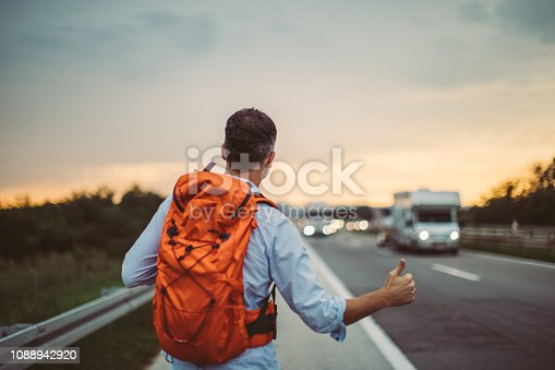 One man, backpacker standing on the highway and hitchhiking, rear view.