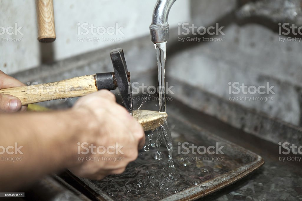 Man hitting a piece of gold while rinsing stock photo