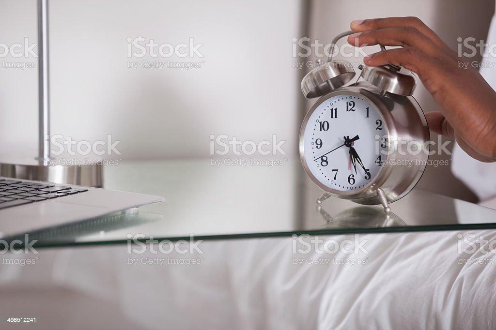 Man hitting his alarm clock stock photo