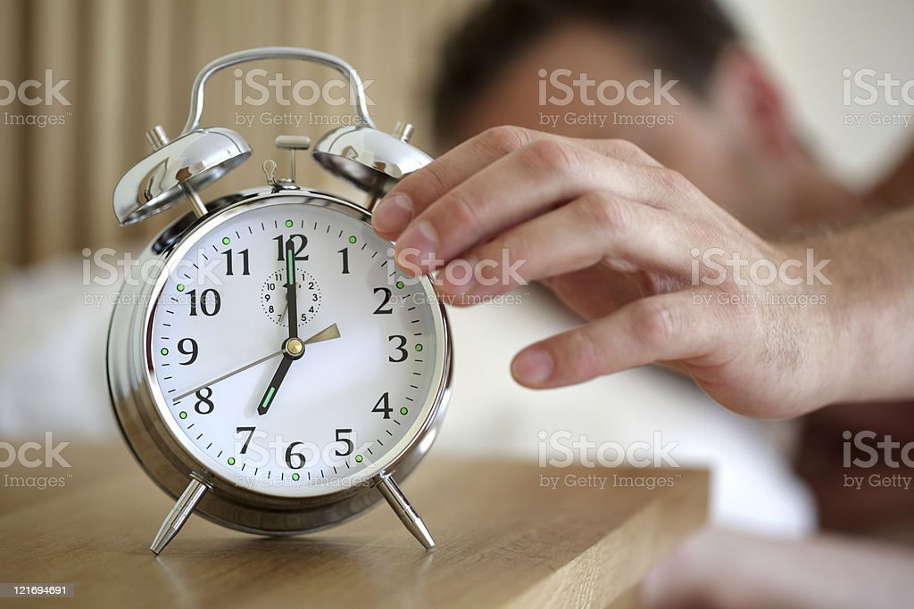 A man hitting the snooze button on his alarm clock  stock photo