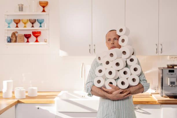 Hombre acaparando papel higiénico sosteniendo muchos rollos - foto de stock