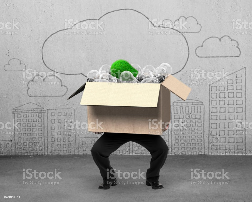 Businessman holding cardboard box with unique green grass bulb among...