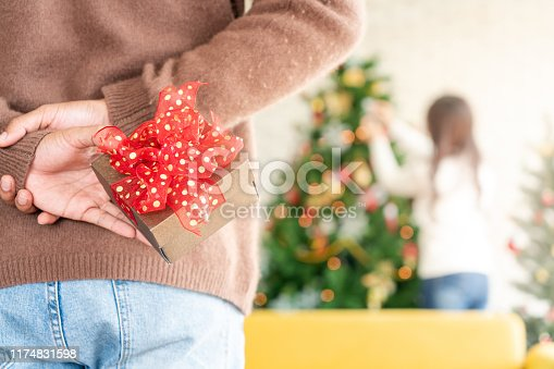 Man hold christmas gift behind his back for surprise his girlfriend while she decorating christmas tree in Chgristmas holiday season greeting.