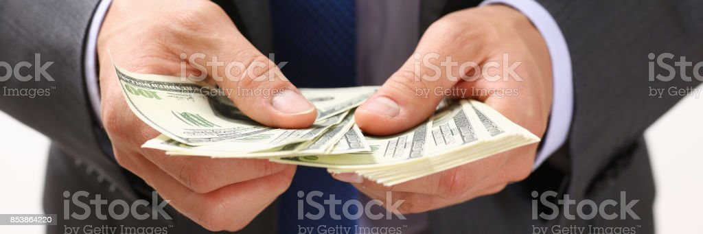 Man hold in arm pack of hundred dollar bills Man in suit and tie hold in arm pack of hundred dollar bills closeup. Stock market, exchange, earn pile, rich present, gift, employer prepayment, service gratitude concept Adult Stock Photo