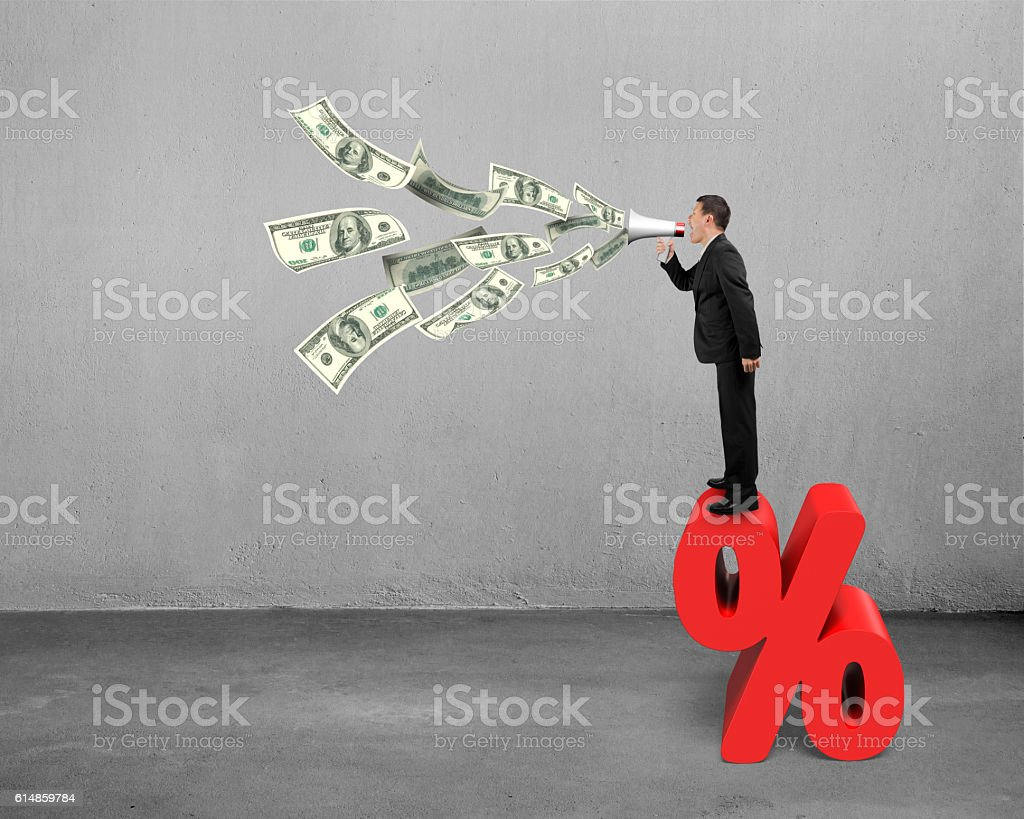 Man hold megaphone spraying out dollar bills on percentage sign stock photo