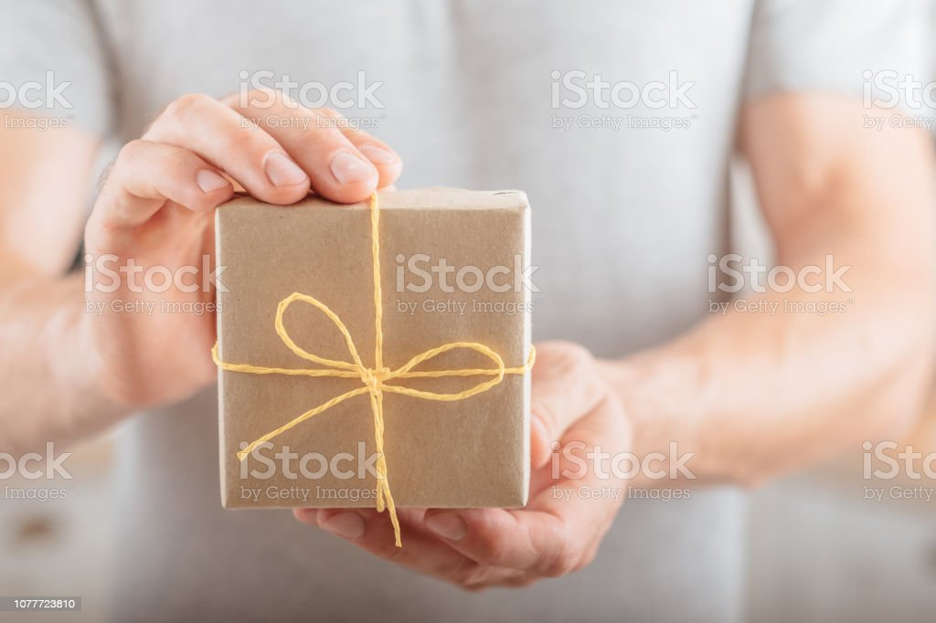 man holding package wrapped in craft paper. online shop order...