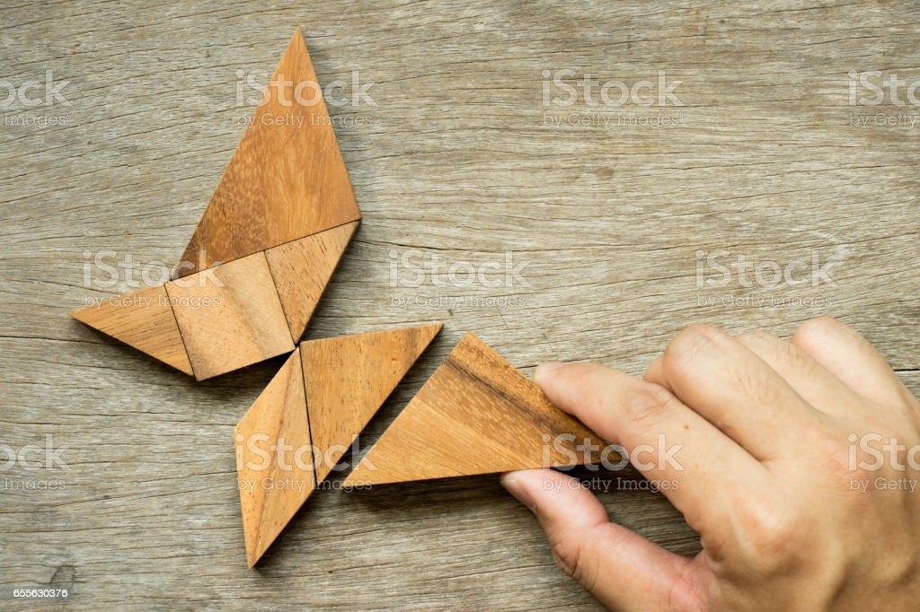 Man hold triangle to fulfill tangram puzzle in butterfly shape (Concept for freedom, free life or explore new world) stock photo