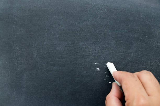 mann halten weißen kreide, etwas am schwarzen brett hintergrund zu schreiben (konzept für geschäft oder bildung von haben platz zum hinzufügen von text) - männer zitate stock-fotos und bilder