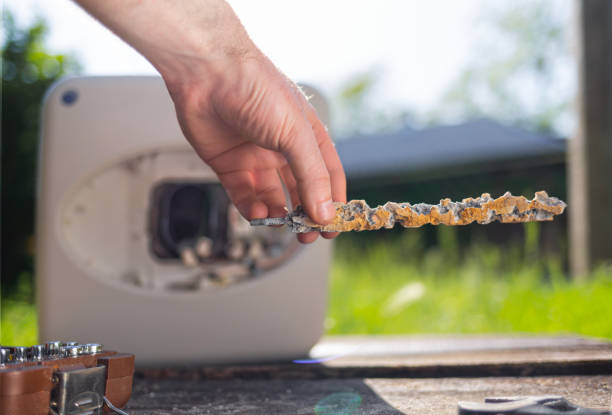 A man holding a anode damaged from corrosion. In the background the boiler with instruments and a view of the lawn. Close up A man holding a anode damaged from corrosion. In the background the boiler with instruments and a view of the lawn. Close up. anode stock pictures, royalty-free photos & images
