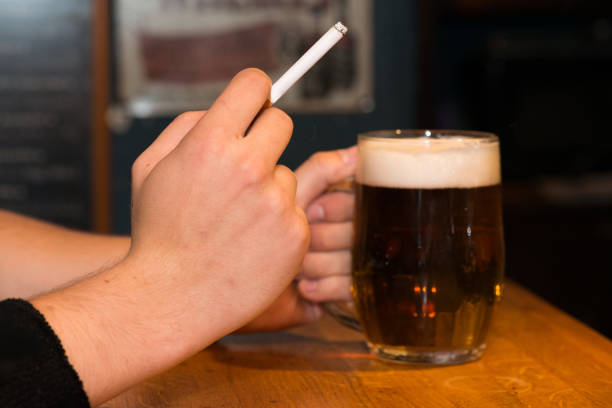 Man holding a beer and cigarette stock photo